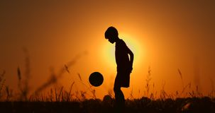 Silhouette of a boy playing football or soccer at the beach with beautiful sunset background Childhood, serenity, sport