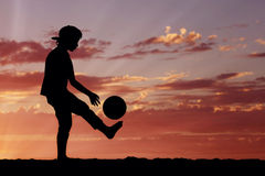 Silhouette of a boy playing football or soccer at Royalty Free Stock Images