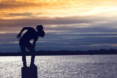 Amazing silhouette of football soccer player boy playing tricks on the beach. In sunset time royalty free stock photos