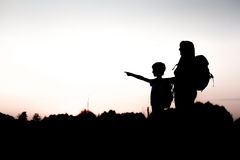 Silhouette of a boy pointing into the distance. Silhouettes of mother and child hiking at sunset. Boy pointing at something distant. Summer vacation in mountains Royalty Free Stock Images