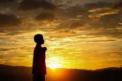 Silhouette boy praying stock photography
