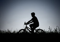 Silhouette of boy riding on bicycle at field Royalty Free Stock Photos