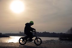 Silhouette of a boy riding a Bicycle in the Park. stock photography