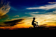 Silhouette of a boy riding a bicycle at sunset in public park. stock photo