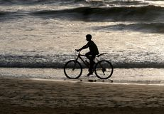 Silhouette of a boy riding a bike along the ocean. After sunset Stock Photo