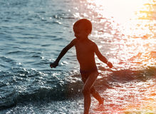 Silhouette of a boy running along the beach Royalty Free Stock Images