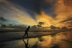 Silhouette Boy Running to Avoid Beach Waves at Dusk with Dramatic Sky Burning. Silhouette of a boy running to avoid the beach waves at dusk with a dramatic sky stock photos