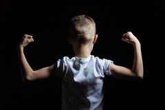 Silhouette of a Boy Showing Arm Muscles Strength Stock Images
