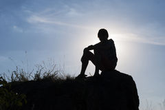 Silhouette of a boy. Sitting boy on the rock stock image