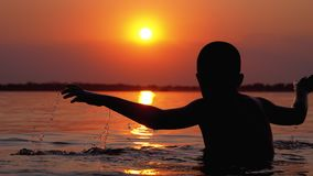 Silhouette of Boy Sitting in the Water on Background of Sunset and Orange Path. Slow Motion. Silhouette of Boy Sitting in the Water on Background of Sunset and stock video