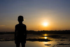 Silhouette of the boy stand watching the sunset on the river Royalty Free Stock Images