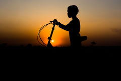 Silhouette of a boy. Standing with a bike on sunset background Stock Photos
