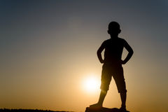 Silhouette of Boy Standing with Hands on Hips Royalty Free Stock Photography