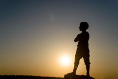 Silhouette of Boy Standing with Hands on Hips Stock Photo