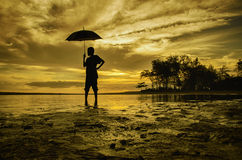 Silhouette a boy standing and look at the back while holding an umbrella Royalty Free Stock Photo