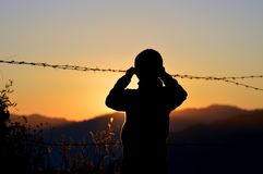 Silhouette of Boy Standing Near Barbed Wire Stock Image