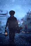 Silhouette of boy, standing on stairs, holding lantern and teddy. Bear, view of Prague behind him, snowy evening Stock Image