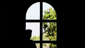 Silhouette of a boy stands near a window and waving hand stock video