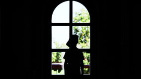 Silhouette of a boy stands near a window and waving hand stock footage