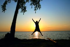 Silhouette of a boy at sunset. Happy person jumping on the sunset sky background Stock Photo