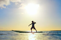 Silhouette of a boy on surfboard Stock Image