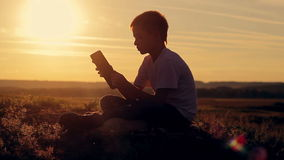Silhouette of a boy with a tablet at sunset. stock footage