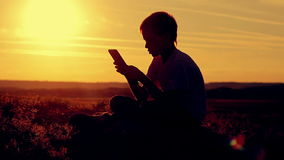 Silhouette of a boy with a tablet at sunset. stock video footage