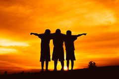 Silhouette boys open arm at sunset or sunrise. Background Royalty Free Stock Photo