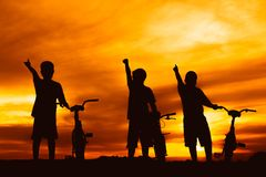 Silhouette boys riding bicycle at sunset or sunrise. Background Royalty Free Stock Image