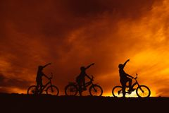 Silhouette boys riding bicycle at sunset or sunrise. Background Royalty Free Stock Photo