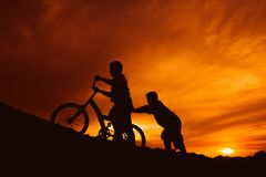 Silhouette boys riding bicycle at sunset or sunrise. Background Stock Photography