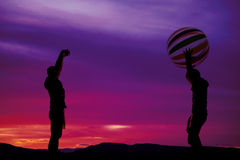 Silhouette of boys throwing a beach ball. Two teenage boys having some fun in the outdoors, playing with a beach ball royalty free stock image