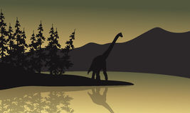 Silhouette of brachiosaurus in riverbank Royalty Free Stock Photos