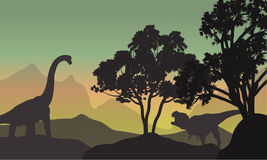 Silhouette of brachiosaurus and T-Rex in hills Stock Photo