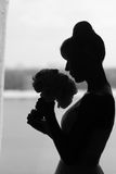Silhouette of bride besides the window Royalty Free Stock Photography