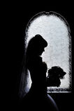 Silhouette of bride besides the window with her wedding bouquet Royalty Free Stock Photo