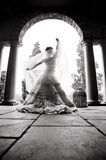 Silhouette of bride dancing under archway. Playing with Veil Royalty Free Stock Photo