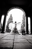 Silhouette of bride dancing under rock archway. Young beautiful bride dancing under rock archway with bird cage Stock Images