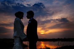 Silhouette of a bride and groom on the background of the evening lake Stock Photo