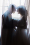 Silhouette of bride and groom embracing holding bouquet against the window with curtains. Silhouette of bride and groom embracing holding hands with bouquet Royalty Free Stock Photo