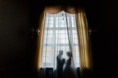 Silhouette of bride and groom embracing holding bouquet against the window with curtains. Silhouette of bride and groom embracing holding hands with bouquet Royalty Free Stock Images