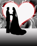 Silhouette Bride and Groom Heart Shaped Moon. Silhouette of Bride and Groom on their wedding day in front of a heart shaped moon with a red glow on a floral rose Royalty Free Stock Photo