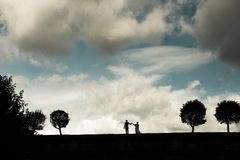 Silhouette of a bride and groom on the horizon Stock Photo