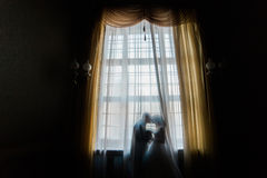 Silhouette of bride and groom kissing against the window with curtains.  Royalty Free Stock Photos
