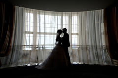 Silhouette bride and groom kissing in front of narrow window Stock Images