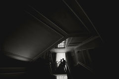 Silhouette bride and groom kissing in front of narrow window.  Stock Photography