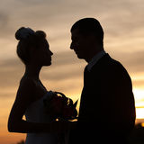 Silhouette of bride and groom over dusk sky Royalty Free Stock Image