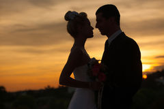 Silhouette of bride and groom over dusk sky Stock Images