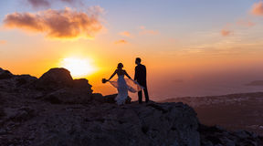 Silhouette of bride and groom on  sea sunset. Silhouette of bride and groom on a high rock on a background of sea sunset Stock Photo