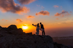 Silhouette of bride and groom on  sea sunset. Silhouette of bride and groom on a high rock on a background of sea sunset Stock Photos